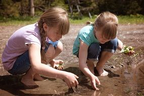 Twins girl playing in water puddle