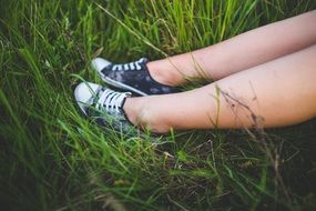 girl in sneakers on a meadow