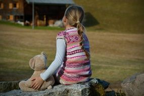 girl and teddy bear soft toy sitting on stone