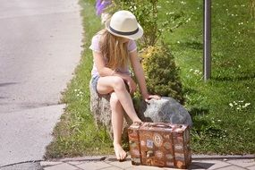 photo of Blonde girl sitting on stone with suitcase