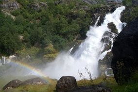 rainbow against the backdrop of a mountain waterfall in Norway