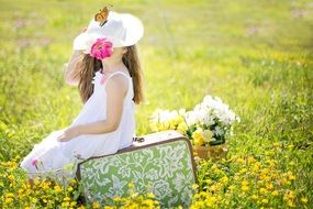 girl on a suitcase in a meadow
