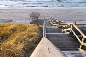 wooden staircase to sand beach at north sea, germany, sylt