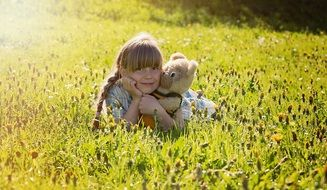 Little girl with a teddy bear among the meadow on a sunny day
