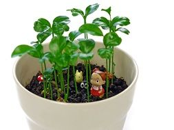 Small figures in a white ceramic pot with green plants