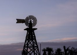 windmill outlines western texas evening sky