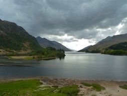 grey clouds above mountain lake at stormy sunset, uk, scotland, glenfinnan
