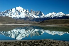 snow-capped mountains are reflected in the water in patagonia