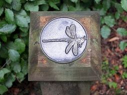 steel dragonfly on a wooden post