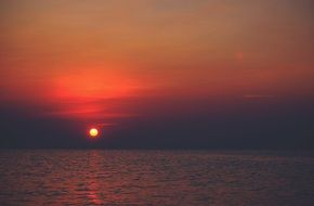 orange sun and pink sunset over the sea