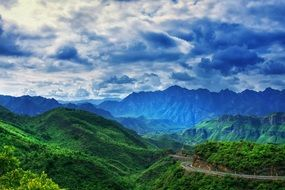 Mountains with green plants under a cloudy sky