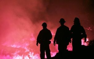 dark silhouettes of firefighters on fire