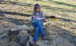 Little girl with a book sitting on a stone