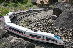model of miniature train going by railways