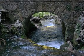 natural stones bridge over a stormy river