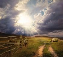 bright sun through stormy clouds over a field