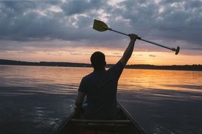 paddler in a boat at sunset