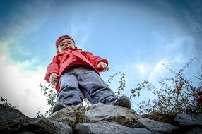 boy in a red cap and a jacket on top of a mountain
