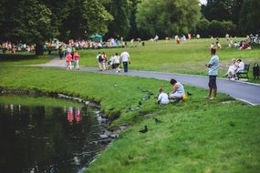 people in park feeding pigeons