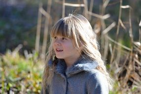 Little girl with long blond hair in a jacket on a sunny day