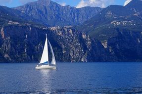 white sailboat in a blue mountain lake in italy
