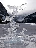 ice carving, human figure with bird and dog on lake louise, canada, alberta