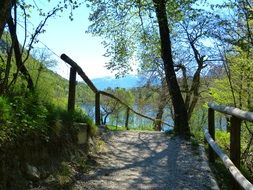 walk path with wooden railing to tenno lake, italy