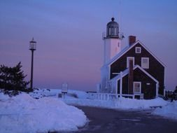 harbor lighthouse in winter against a purple sky