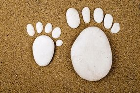 stone installation of footprints in the sand