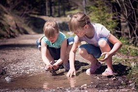 blonde girls taking stones in puddle