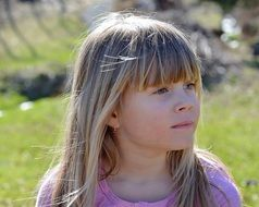 Pensive face of a little girl with long blond hair