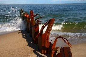 rusty remains of pier on beach at sea, germany, sylt