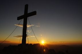 silhouette of the cross against the sunset