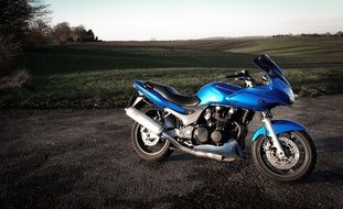 blue chromed motorcycle in the countryside