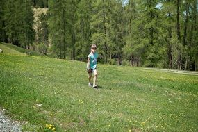 child runs in a green meadow