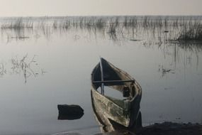 weathered rowing boat on calm water at shore