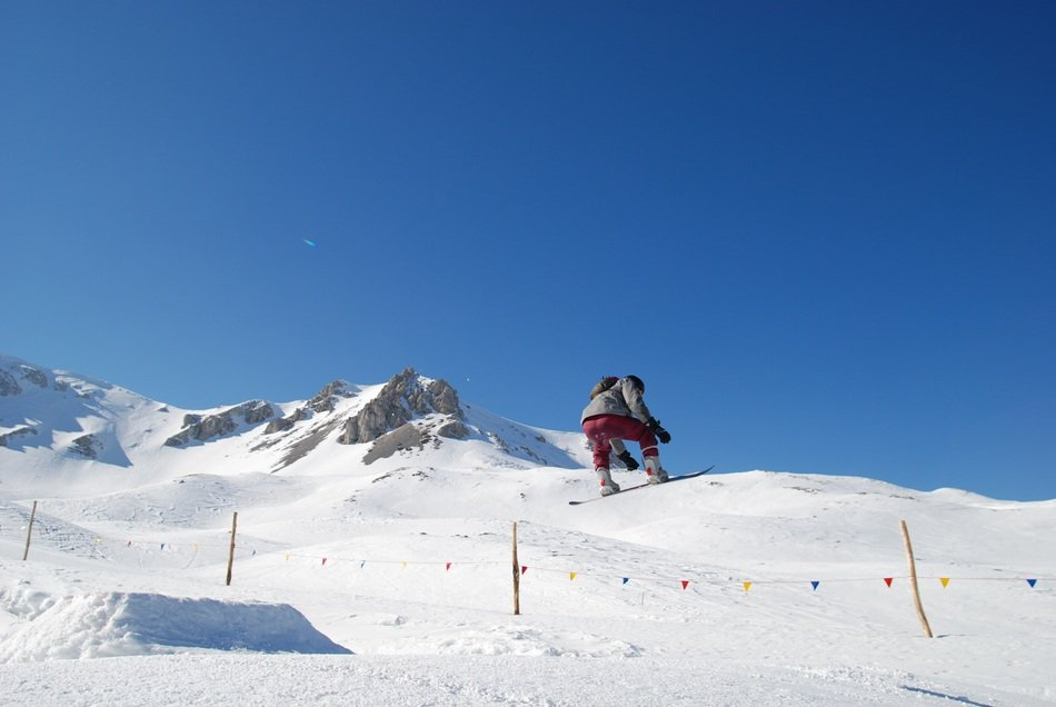 snowboarder jumping on snowy mountain