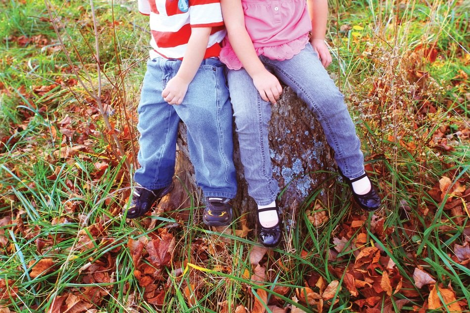 two children on a stump among autumn nature