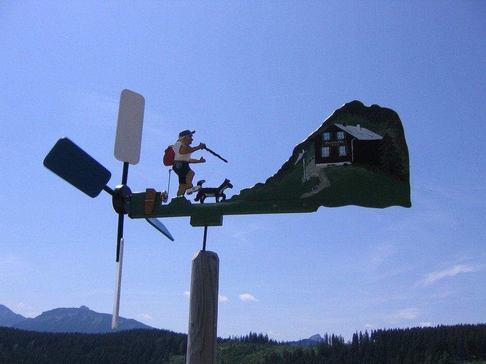 funny tourist, wind vane at mountain landscape