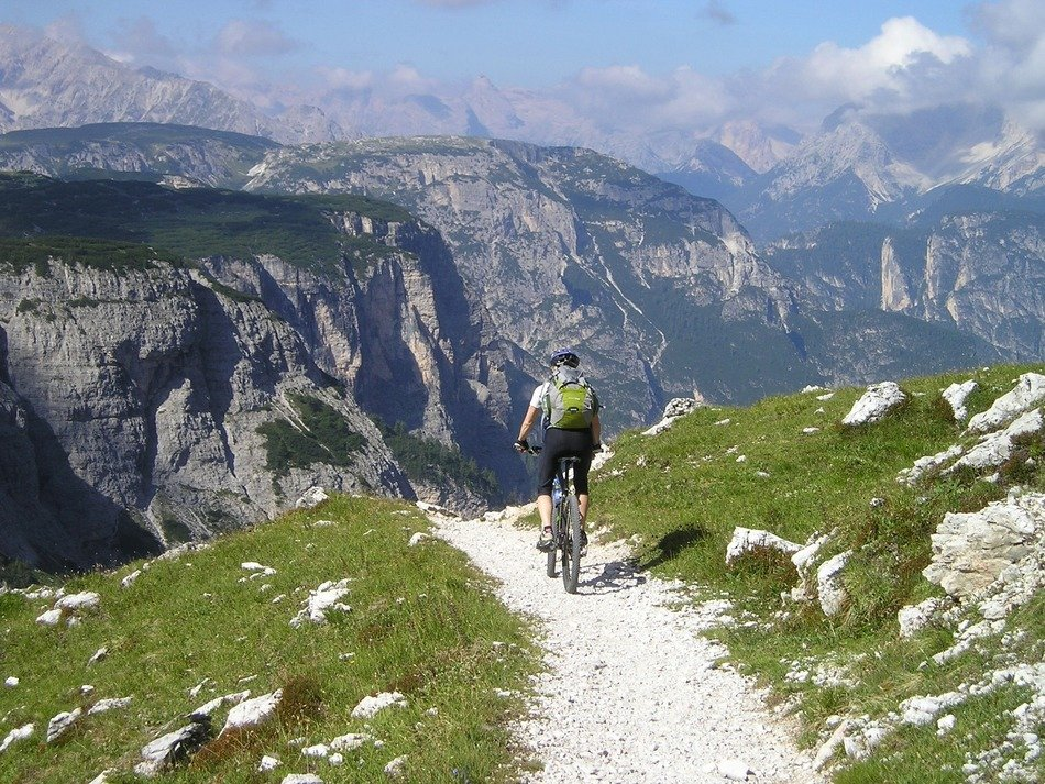 cyclist with a backpack on a path in the mountains of south tyrol