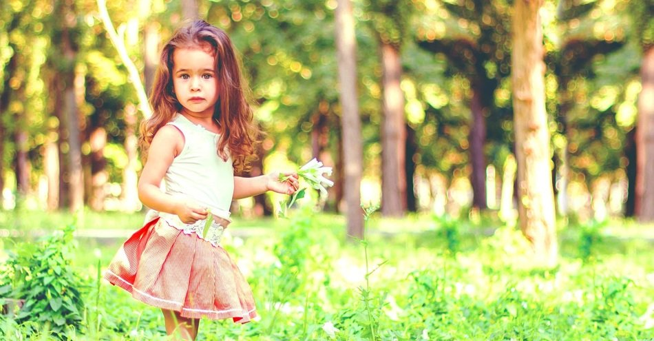 little girl standing on green grass