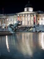 fountain in front of national gallery on trafalgar square at night, uk, england, london