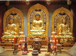 three golden Bodhisattva statues in a temple in China