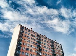 sky with white clouds over an apartment building