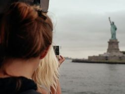 girl looks at the statue of liberty