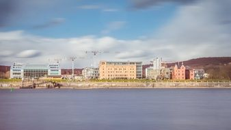 cranes at buildings under construction on bank of rhine river, architecture panorama, germany, bonn