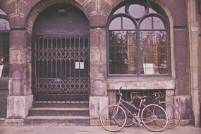 bicycles are parked under the window of a historic building