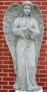 statue of an angel near a brick wall