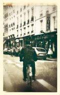 black and white photo of a cyclist on a street in Paris