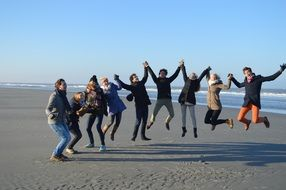 People jumping on seashore